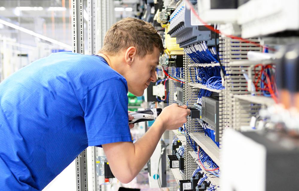 Elektroniker montiert Anlage in einer Maschinenbaufabrik