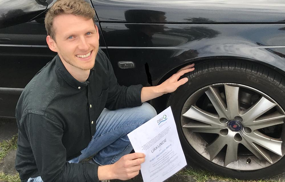 Robin Bähre mit seiner DBU-Urkunde vor einem Autoreifen – einem von vielen Gummireifen, deren Abrieb er untersuchen wird. (Foto: IKK)