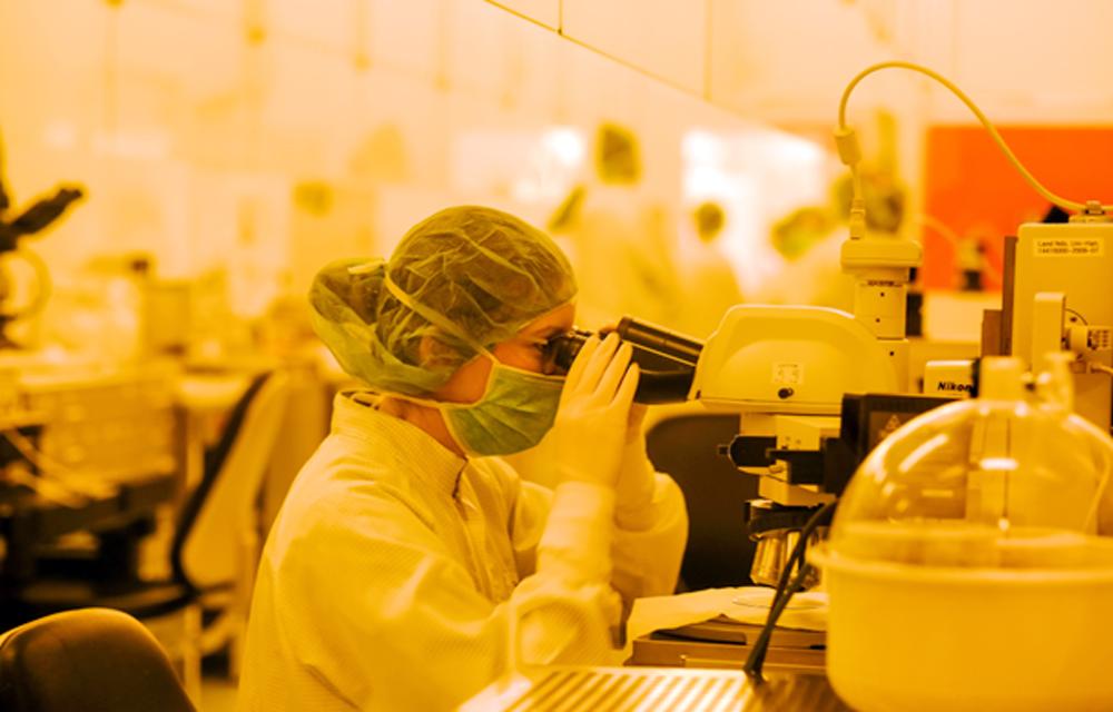 Eine Schülerin betrachtet im Reinraum des IMPT einen Siliziumwafer mit Sensoren unter dem Mikroskop. (Foto: China Hopson)